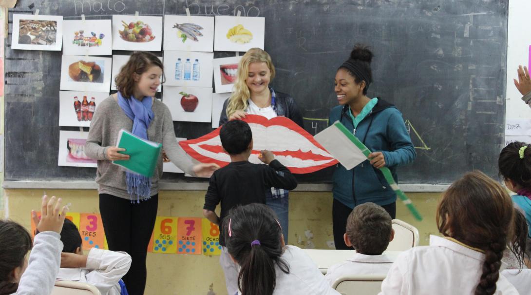 Jóvenes voluntarias le enseñan a los niños sobre higiene bucal durante su voluntariado social en verano.